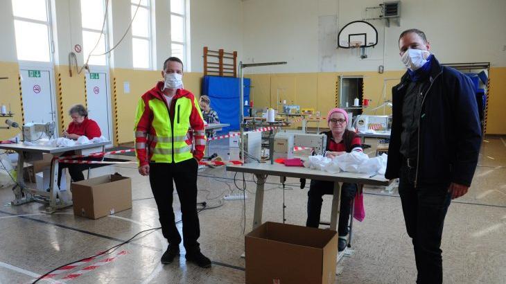 """Dominik Berger (links), Chef von Sutura, und Bürgermeister Frank Pitterlein testen die Masken der Helferinnen am neuen Standort """"Schnaittacher Turnhalle""""."""
