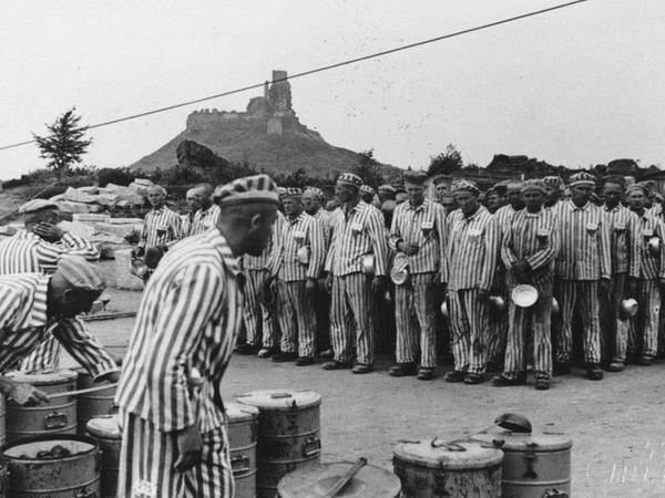 Verteilung von Essen an Häftlinge im Steinbruch des KZ (im Hintergrund die Flossenbürger Burg). Die von ihnen abgebauten Granitsteine wurden unter anderem für den Bau des Reichsparteitagsgeländes in Nürnberg benötigt.