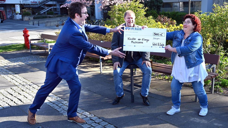 Abstands-Freude: Sonja Tonn und Wulli Wullschläger (hinten) überreichen den Künstler-Scheck über 5000 Euro zur Verteilung an Oberbürgermeister Florian Janik.