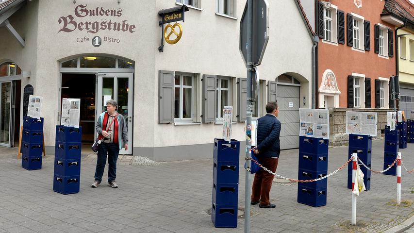 Corona-Shutdown, Tag 32: Gute Idee der Gulden-Bäckerei, das Warten unterhaltsam zu machen: Auf Kistenstapeln in korrektem Abstand ist jeweils eine Doppelseite der Erlanger Nachrichten lesefertig montiert.
