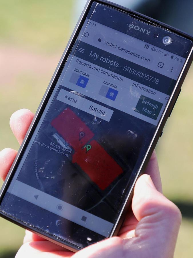 """Auf seinem Handy kann Fußballabteilungsleiter Dieter Kupfer sehen, wie weit """"Big Mow"""" mit seiner Arbeit ist – rot markiert sind die bereits gemähten Flächen."""