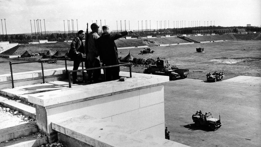 Angehörige der US-Armee auf dem Reichsparteitagsgelände. Als eine der ersten Amtshandlungen wurde das riesige Hakenkreuz an dr Tribüne weggesprengt.
