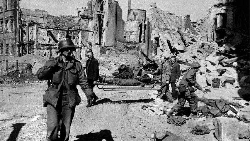 Dieses Foto entstand am 19. April 1945 in Nürnberg. Zivilisten bringen einen Verletzten in Sicherheit. Im Vordergrund streift ein GI durch die zerstörte  Stadt.