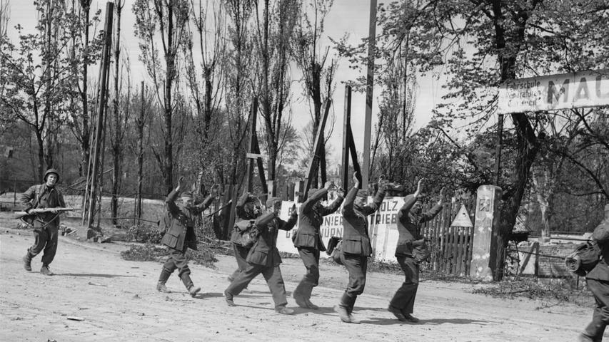 Ein amerikanischer Soldat bringt deutsche Landser in ein Kriegsgefangenenlager. Die Männer sollten laut Befehl den Einmarsch der US.Armee verhindern, mussten aber schnell einsehen, dass der Feind überlegen war.