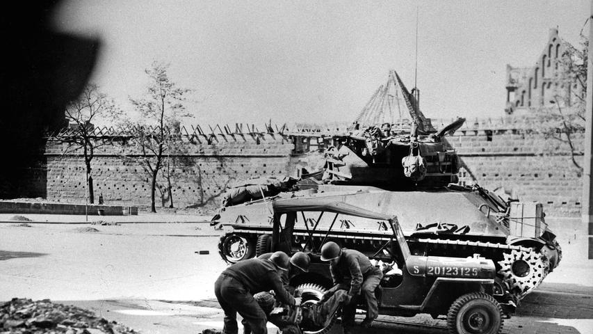 Das Bild zeigt die Dramatik der letzten Kriegsstunden in Nürnberg. US-Soldaten transportieren im Schutz eines Panzers einen verletzten Kameraden ab. Die Szene wurde am Frauentorgraben aufgenommen.