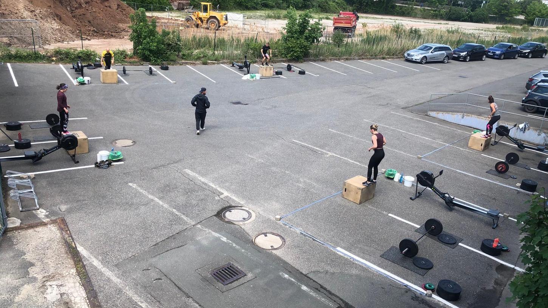 Rudern, Boxjumps und Power Cleans: Daniel Sandreuther (Mitte) inmitten eines Kleingruppen-Workouts im Freien auf dem Parkplatz vor seiner Crossfit-Box.