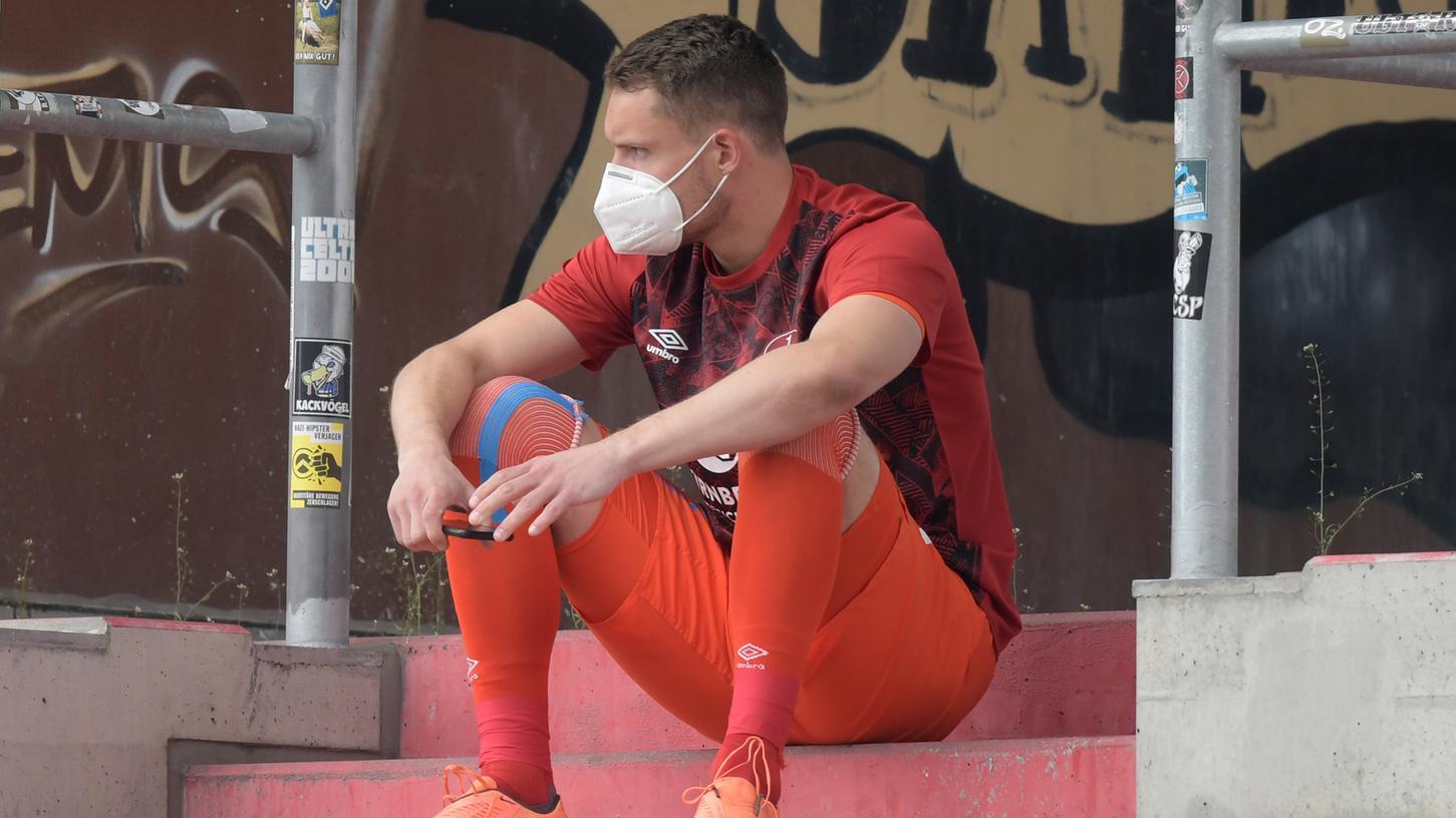Christian Mathenia sitzt nach seiner Roten Karte mit Maske auf der Tribüne des Millerntor-Stadions.