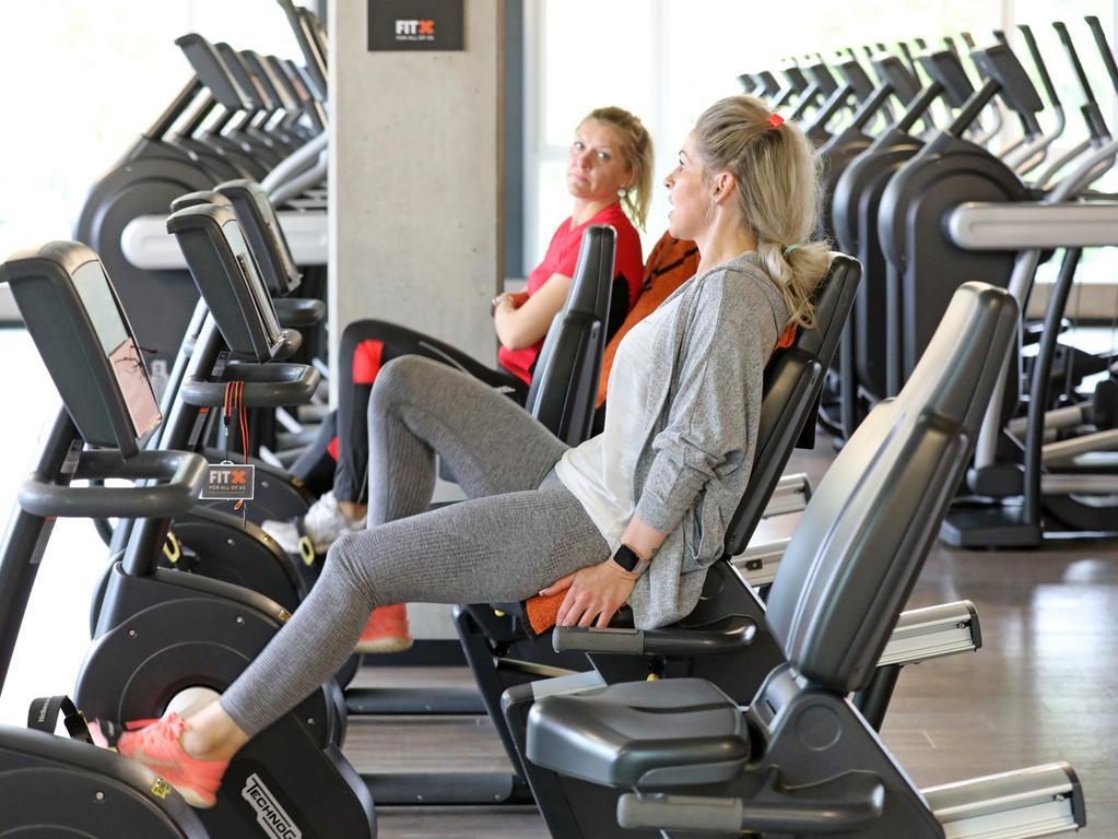 25.05.2020, Mecklenburg-Vorpommern, Rostock: Zwei Frauen trainieren im Fitnessstudio FitX. Fitnessstudios und Sporthallen in Mecklenburg-Vorpommern dürfen ab dem 25.05.2020 unter Auflagen wieder öffnen. Foto: Bernd Wüstneck/dpa-Zentralbild/dpa +++ dpa-Bildfunk +++