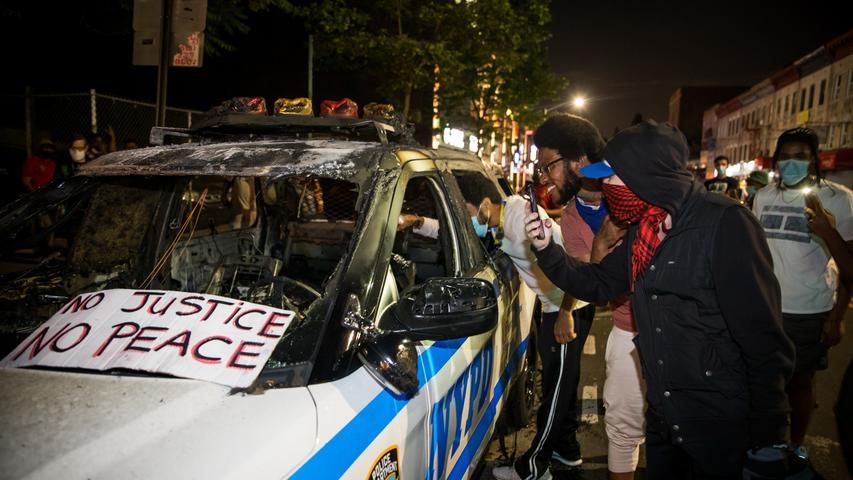 30.05.2020, USA, New York: Demonstranten betrachten ein verbranntes Fahrzeug der New Yorker Polizei, auf dem ein Schild mit der Aufschrift