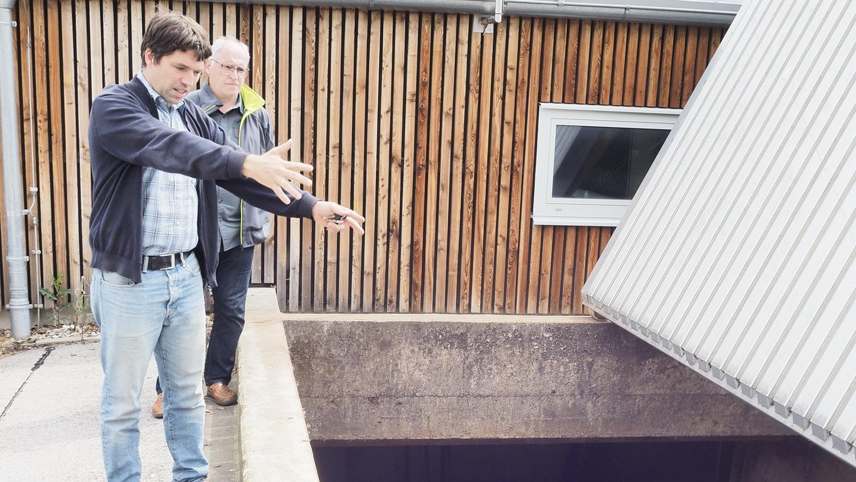 Fabian Röhnisch (vorne) und Alfred Maderer von der FBG stehen vor dem Hackschnitzelbunker der Anlage. Im Sommer sorgt ein Gasbrennkessel für Wärme.