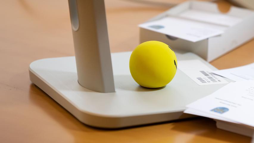 Auf dem Schreibtisch liegt ein Smiley-Ball.