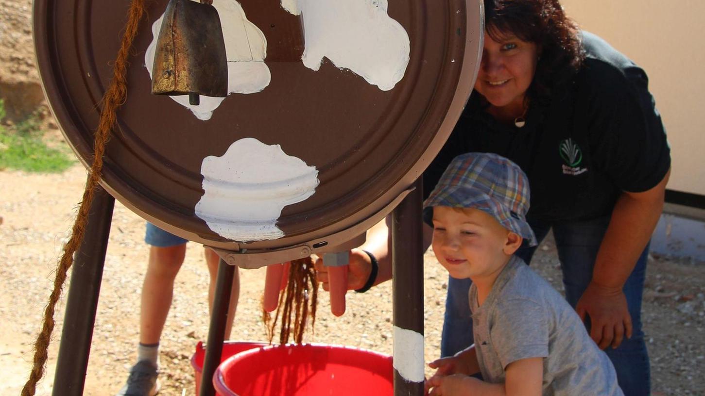 Kreisbäuerin Bettina Hechtel und ihr Enkel zeigen, wie ein Melkautomat aussehen könnte, der am Weg der Landwirtschaft stehen soll.