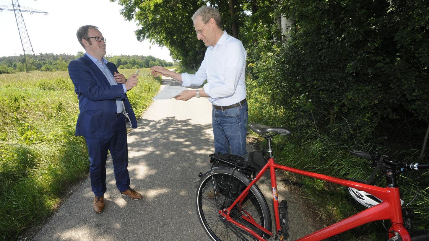 Bürgermeister Florian Janik reicht seinem Amtskollegen German Hacker einen Stift, damit auch der den Fördermittelantrag für die Planungskosten unterschrieben kann. Der Sattel dient als Schreibtisch.