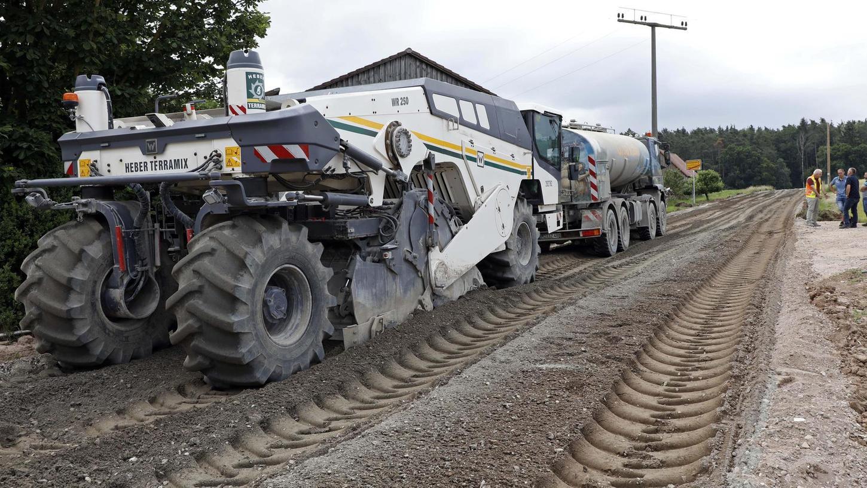 Mit der Maschine wird das Bindemittel ins zerkleinerte Straßenmaterial eingebracht. Davor das Wasser-Fahrzeug.