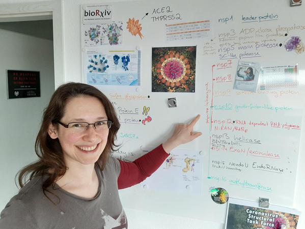 Strukturbiologin Andrea Thorn vor einer Tafel in ihrem Homeoffice, von dem aus sie ein internationales Team von Spitzenkräften im Kampf gegen das Coronavirus koordiniert.
