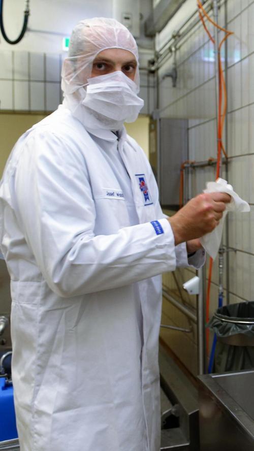 In der Fleischverarbeiterfirma Wolf, die pro Jahr rund 171 Millionen der Würste produziert, desinfiziert jeder Mitarbeiter zum Schichtbeginn seine Hände und Schuhe. Nach Schichtende wird die Kleidung gewaschen.