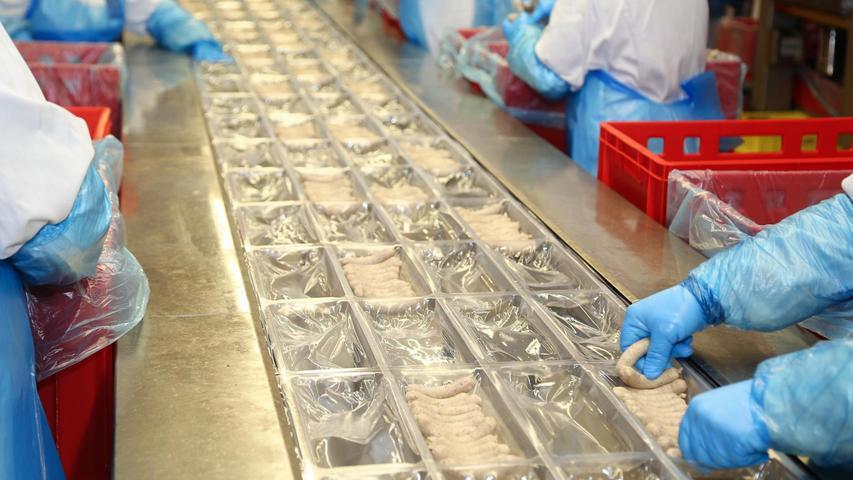 Das Verpacken der Nürnberger Rostbratwürste geschieht bei der Firma Wolf per Hand oder mit Hilfe eines Pick-and-Place-Roboters. In einem Nebenraum werden per Hand kleinere Chargen für Gastronomie-Betriebe oder Möbelhäuser abgepackt.