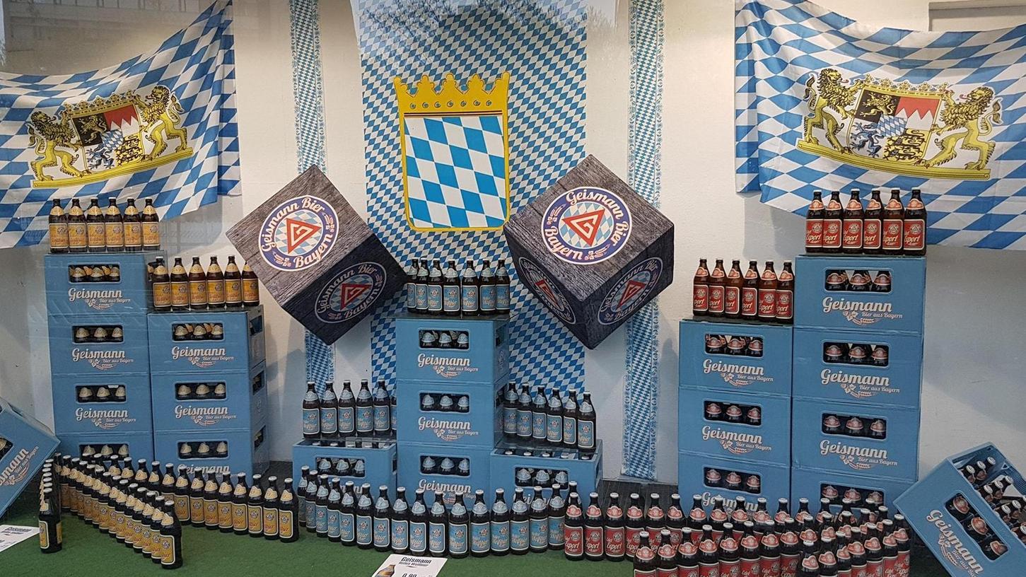 """Ein Schaufenster in der Berliner Kurfürstenstraße preist Geismann-Bier an. Das weiße """"G"""" im roten Dreieck lässt auf Fürther Brautradition schließen. Über allem weht die Bayern-Fahne."""