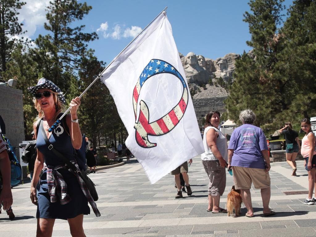 KEYSTONE, SOUTH DAKOTA - JULY 01: A Donald Trump supporter holding a QAnon flag visits Mount Rushmore National Monument on July 01, 2020 in Keystone, South Dakota. President Donald Trump is expected to visit the monument and make remarks before the start of a fireworks display on July 3.   Scott Olson/Getty Images/AFP == FOR NEWSPAPERS, INTERNET, TELCOS & TELEVISION USE ONLY ==