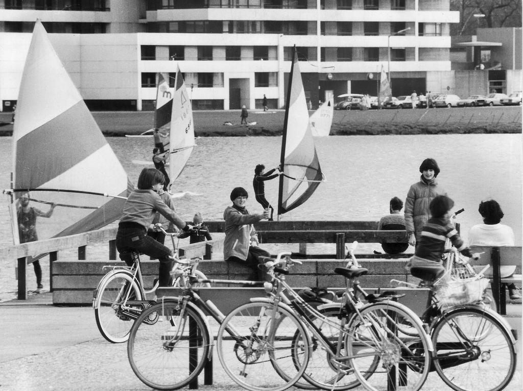 FOTO: NN, Friedl Ulrich, veröff. 18./19.04.1982, 1980er, historisch...MOTIV: Surfer, Surfbretter, , Radfahrer,abgestellte Fahrräder, Spaziergänger und Erholungssuchende (sitzend) am Ufer Wöhrder See. Blick auf den Noricus in Nürnberg...KONTEXT 1974..