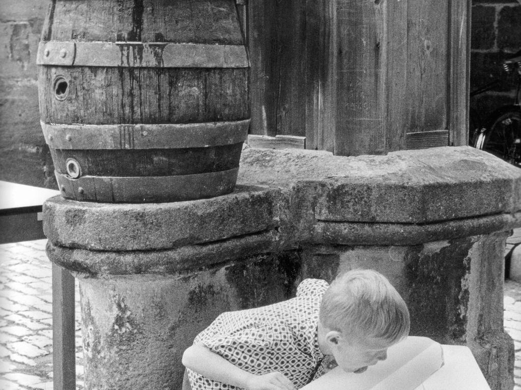 Ein kleiner Junge schleckt an einem Eisblock, der zum Kühlen von Holzfässern voller Bier verwendet wird. Eis, Kind; Sommer, Hitze; F.: Hans Kammler, Erstveröffentlichung am 14. Juli 1970.
