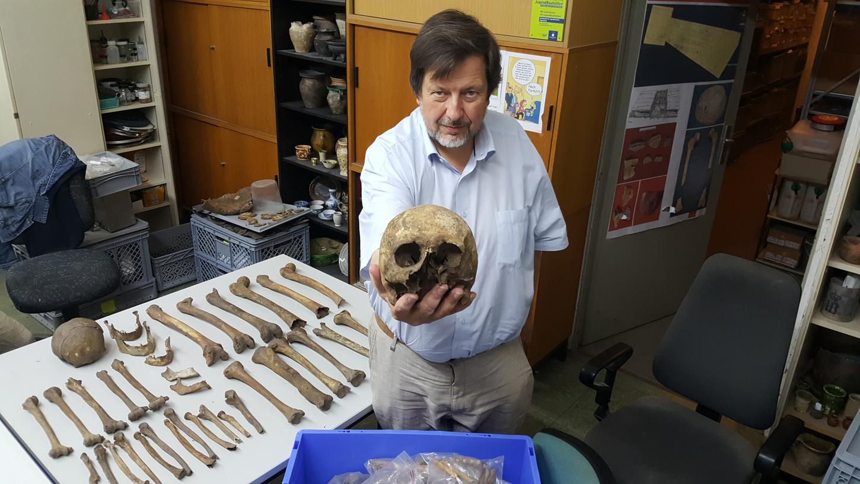 Stadtarchäologe John Zeitler präsentiert den Schädel eines Verstorbenen, der bei Erdarbeiten am Lärmschutzwall entlang der Südwesttangente zum Vorschein kam - genau wie die am Tisch aufgereihten menschlichen Knochen.