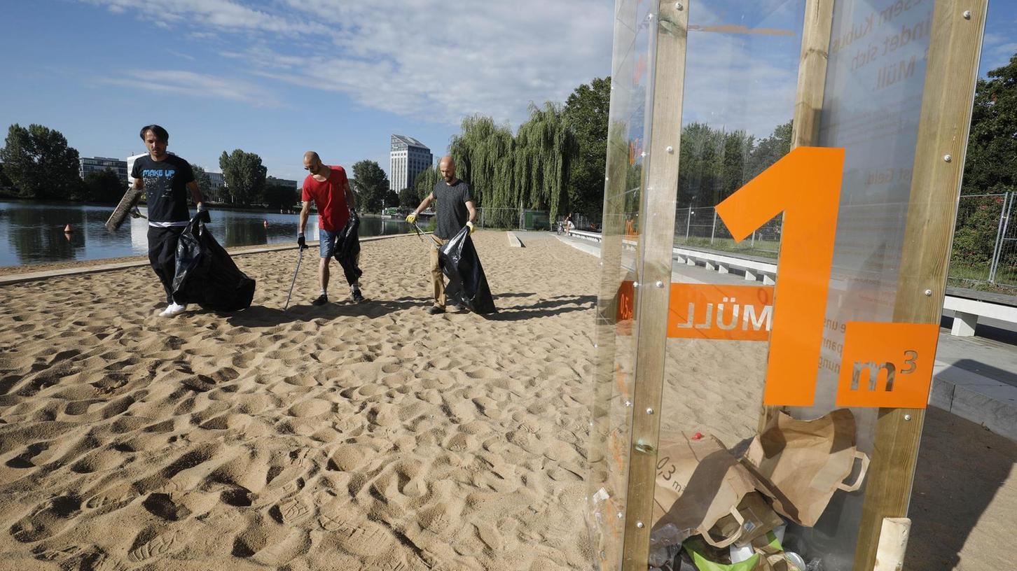 Sör-Mitarbeiter sammelten am Samstagvormittag auf dem Sandstrand Abfall auf und warfen ihn in den durchsichtigen Müll-Kubus.