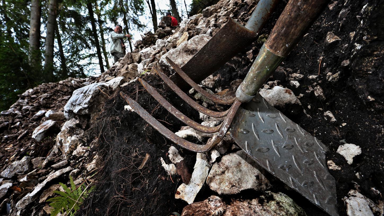 Eine Hacke und ein Spaten liegen an einem von einem Bagger abgetragenen Steilhang auf dem Falkenstein. Schatzsucher hatten dort gegraben, bis der Boden abzurutschen drohte.