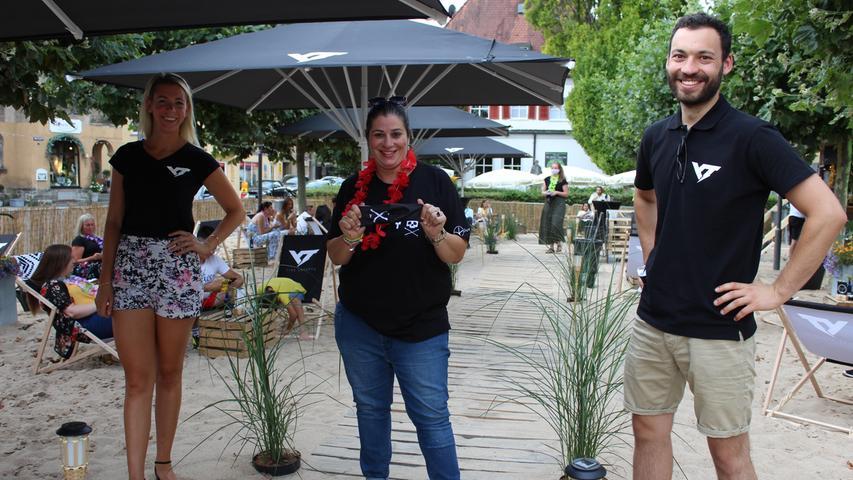 """Am Samstagabend war es soweit: Auf dem Forchheimer Marktplatz hat der Stadtstrand alias """"Antonellas Stadtstrand"""" geöffnet. In Kürze waren die 50 Plätze zwischen Sand und Bäumen vergeben. Liegestühle, 30 Grad, kühle Getränke und Live-Musik sorgten für Sommergefühle und gute Laune bei den Gästen. Die Organisatoren Antonella Pileio, Nicholas Mohnlein und Louisa Herold waren stolz, dieses Projekt in Kürze auf die Beine gestellt zu haben."""