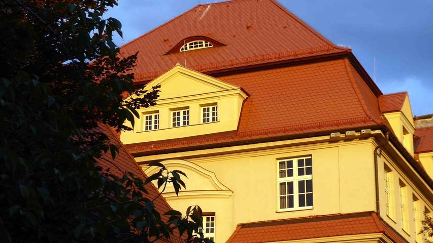 …der Schirm letztlich bei strahlender Abendsonne auf der sanierten Fassade der Schloss-Grundschule lediglich als Deko.