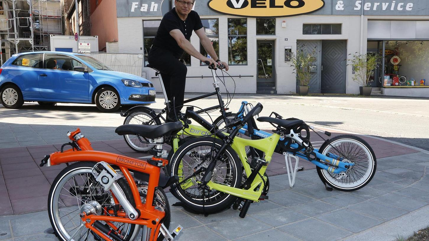 """So schauen sie aus, wenn sie klein """"gefaltet"""" sind: NN-Redakteur Jo Seuß begutachtet, auf einem Velo-Faltrad aus Wien sitzend, die drei Marken des Velo-Ladens (v. li.) namens Brompton, Birdy und Strida."""