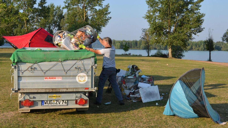 Vorsicht, Wespengefahr: Die Mülleimer, die hier auf die Ladefläche entleert werden, sind umschwirrt von den lästigen Plagegeistern. Die fleißigen Mülleinsammler ertragen das mit stoischer Ruhe.