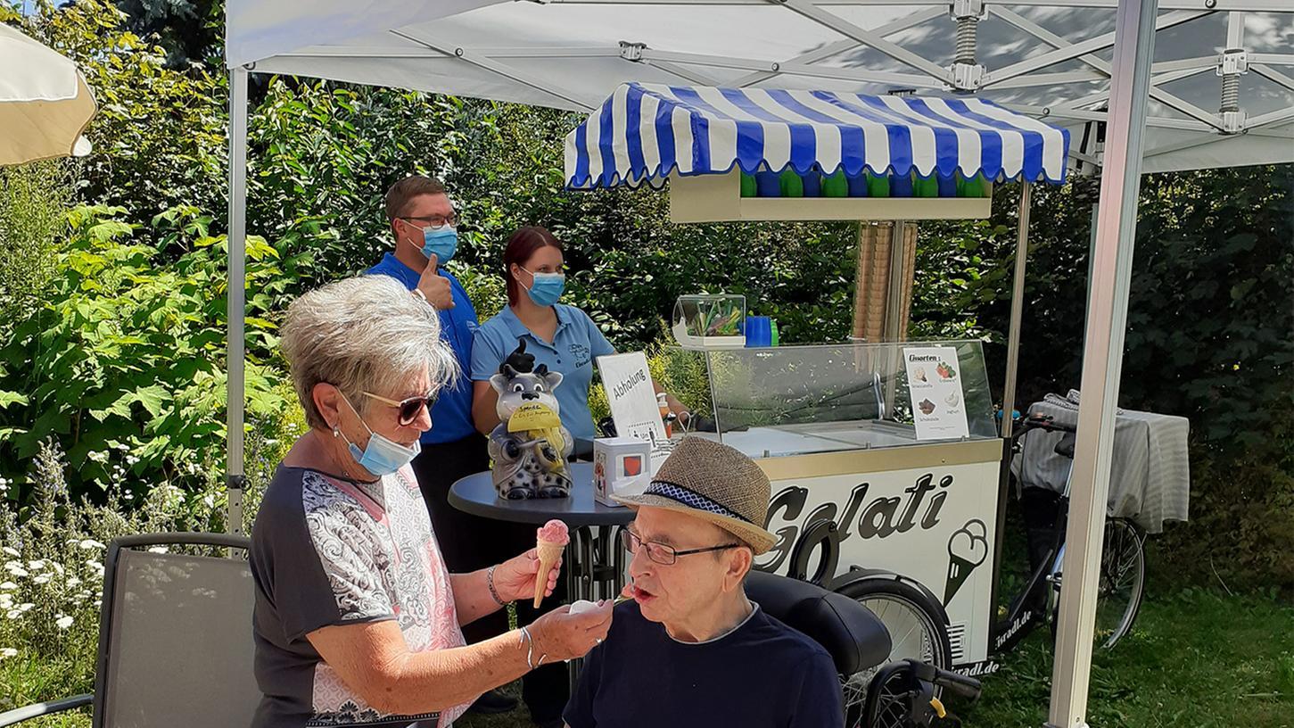 """Ein Bewohner im Kompetenzzentrum lässt sich mit seiner Ehefrau ein Eis schmecken. Virginia und Daniel Metzger (im Hintergrund), die das """"Eisradl"""" als Familienunternehmen betreiben, freuten sich über die gelungene Überraschung."""