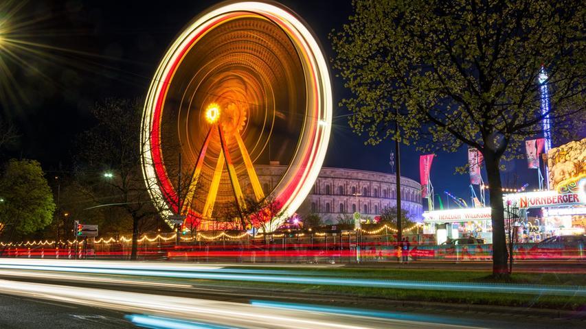 Das Volksfest am Dutzendteich erstrahlt am schönsten bei Nacht, im Hintergrund ist das Reichsparteitagsgelände zu sehen.