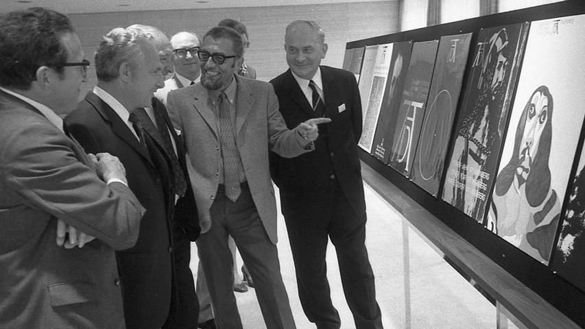 Die Jury bei ihrem Rundgang: Sachpreisrichter Otto Peter Görl deutet amüsiert auf einen Plakatentwurf mit einem Dürer-Selbstbildnis, abgewandelt zur Cocker-Spaniel-Physiognomie. Hier geht es zum Kalenderblatt vom22. August 1970: Dürers Hase im Pop-Stil.