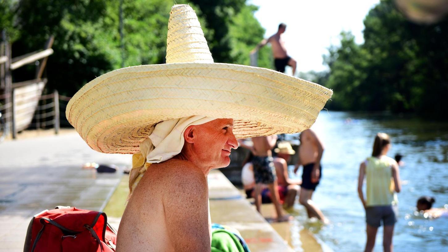 Manche sonnen sich nur, viele aber tauchen ein: Trotz Badeverbots erfreut sich die Abkühlung an der Uferpromenade in Fürth großer Beliebtheit.