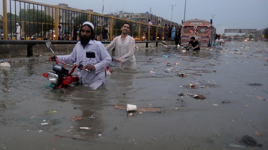Es ist Regenzeit in weiten Teilen Asiens. Seit Tagen fallen vielerorts heftige Niederschläge. In der indischen Hauptstadt Neu Delhi sind viele Straßen bereits großflächig überschwemmt. Im Nachbarland Pakistan sind nach tagelangem Starkregen mindestens 17 Menschen ums Leben gekommen. Unser Bild zeigt Motorradfahrer in Karatschi, die ihre Fahrzeuge über eine Straße schieben müssen, die aufgrund von starken Regenfällen überflutet ist. Auch in China haben die saisonalen Regenfälle ganze Großstädte unter Wasser gesetzt. Am gigantischen Drei-Schluchten-Staudamm wurde der bislang höchste Pegel gemessen.