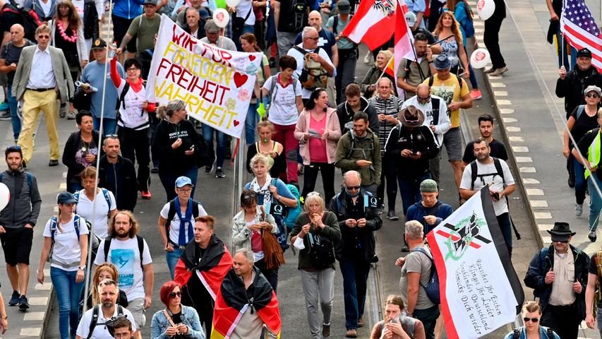 People hold banners and an old nationalist flag (R) during a demonstration called by far-right and COVID-19 deniers to protest against restrictions related to the new coronavirus pandemic, on August 29, 2020 in Berlin. (Photo by John MACDOUGALL / AFP)