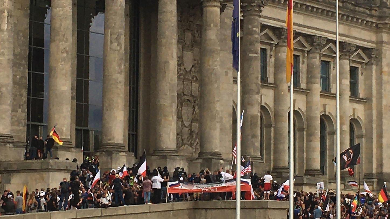 Teilnehmer einer Kundgebung gegen die Corona-Maßnahmen stehen vor dem Reichstag