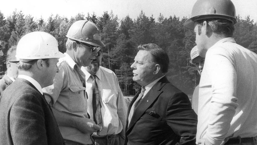 """Weil bis dahin alle Löschversuche gescheitert waren, rief die Betreiberfirma Ruhrgas AG den US-amerikanischen Feuerwehrmann Paul Neal Adair zu Hilfe. Er hatte sich einen Namen mit spektakulären Brandbekämpungsmethoden gemacht. Wegen seiner roten Haare und weil er immer einen roten Overall trug, wurde er allseits nur """"Red Adair"""" genannt. Mit seiner gleichnamigen Firma war er auf die Löschung brennender Öl- und Gasquellen spezialisiert. Der berühmte Mann aus Texas (ohne Helm)verschaffte sich im oberpfälzischen Eschenfelden mit den Technikern der Ruhrgas AG einen ersten Überblick."""