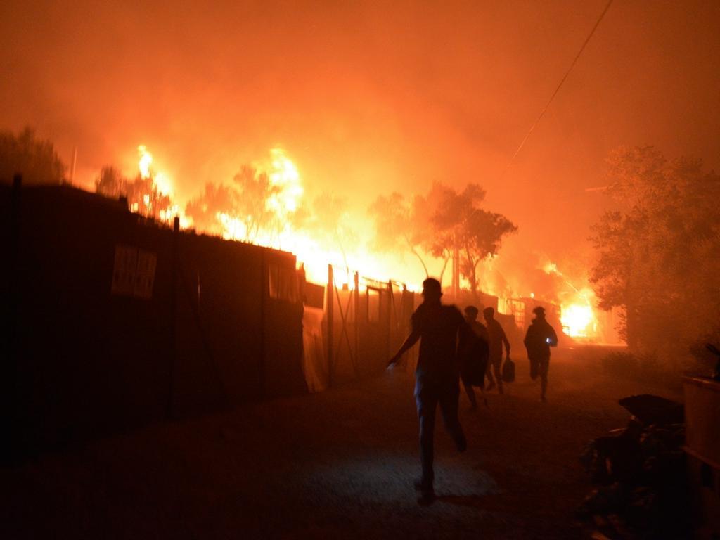 dpatopbilder - 09.09.2020, Griechenland, Lesbos: Geflüchtete rennen während ein Feuer im Flüchtlingslager Moria auf der Insel Lesbos brennt. Medienberichten zufolge stehen auch Wohncontainer in Flammen, weshalb die Behörden das Lager evakuierten. Foto: Panagiotis Balaskas/AP/dpa +++ dpa-Bildfunk +++