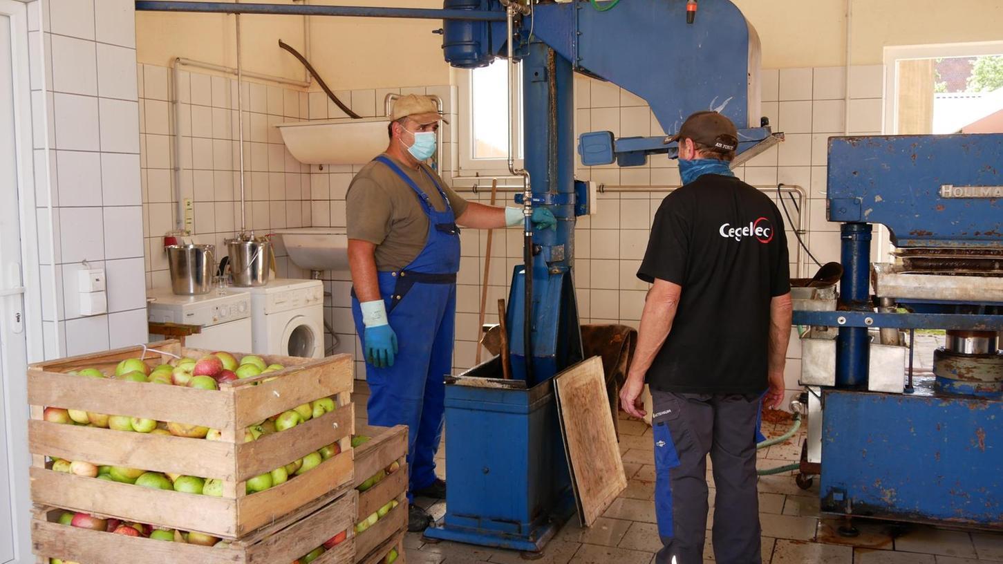 Stefan Müller (links) hat an der Apfelpresse alle Hände voll zu tun. Aus 100 Kilogramm Äpfel lassen sich erfahrungsgemäß 60 bis 70 Liter Saft herauspressen.