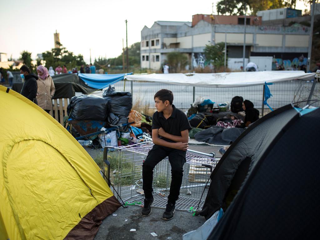 dpatopbilder - 11.09.2020, Griechenland, Moria: Ein Kind sitzt am Rande einer Straße in der Nähe des ausgebrannten Flüchtlingslagers Moria. Mehrere Brände haben das Lager fast vollständig zerstört. Laut griechischer Regierung haben Migranten den Brand gelegt. Das Lager ist eigentlich auf 2800 Bewohner ausgelegt, zuletzt lebten dort aber mehr als 12 000 Migranten. Foto: Socrates Baltagiannis/dpa +++ dpa-Bildfunk +++