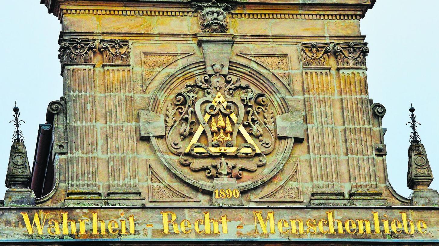 """Am Haus der Loge """"Libanon zu den 3 Cedern"""" in der Universitätsstraße 25 sind neben dem Zeichen der Erlanger Freimaurerloge, die 1741 gegründet wurde und damit die zweitälteste Loge Bayern ist, auch die humanitären Grundsätze der Freimauererei, Wahrheit – Recht – Menschenliebe, zu sehen."""