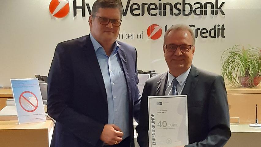 """Die HypoVereinsbank Roth hat seinen Mitarbeiter Jürgen Wießner für seine 40-jährige Treue zum Unternehmen geehrt. Markus Raetsch, Filialleiter der HypoVereinsbank in Roth, überbrachte die Glückwünsche und bedankte sich für den Einsatz von Jürgen Wießner im Laufe der vergangenen 40 Jahre. """"Jürgen Wießner ist mit seiner 40-jährigen Erfahrung ein ausgewiesener Privatkundenexperte mit einer herausragenden Marktkenntnis der Region"""", so Markus Raetsch. """"Mit seiner Loyalität und seinem langjährigen persönlichen Engagement hat Jürgen Wießner einen wichtigen Beitrag zum Erfolg der Bank geleistet."""" Jürgen Wießner begann seine Ausbildung zum Bankkaufmann 1980 in Roth bei der Bayerischen Hypotheken- und Wechselbank. Seitdem war er unter anderem in der Filiale in Neumarkt und der Filiale Nürnberg Königstraße tätig. Seit 1991 ist Jürgen Wießner in der Filiale Roth im Privatkundengeschäft beschäftigt."""