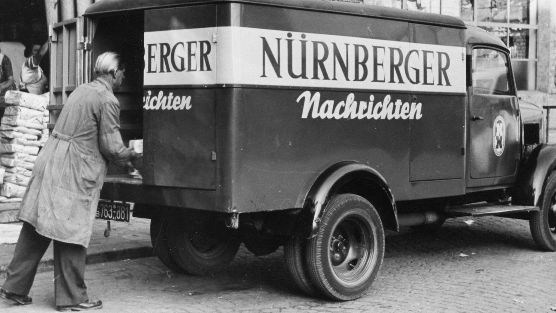 """Ein Lieferwagen wird in den 1950er Jahren mit frisch gedruckten Exemplaren der """"Nürnberger Nachrichten"""" beladen."""