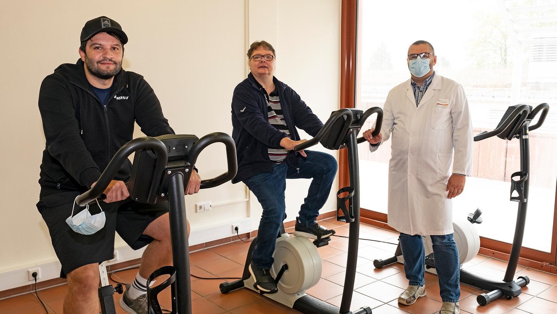 Regelmäßige Einheiten auf dem Ergometer gehören zum Reha-Programm, mit dem Florian Lanz (links) und Andreas Fendius – hier zusammen mit Chefarzt Thomas Fink - die Folgen ihrer Covid-19-Erkrankungen für ihre körperliche Fitness bekämpfen wollen.