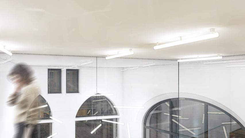 Das Foyer im OG schwebt in den Eingangsbereich (im EG) hinein. Eine Komplettverglasung ermöglicht den Blick von dort auf den darunterliegenden Eingangsbereich.
