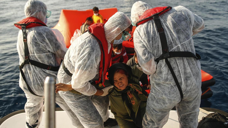 Retter holen eine Frau bei einem Einsatz im Mittelmeer von einem Boot. Auch die evangelische Kirche unterstützt im Bündnis United4Rescue die zivile Seenotrettung mit einem kirchlichen Schiff. Dagegen argumentiert jetzt gewagt ein Nürnberger Theologe.