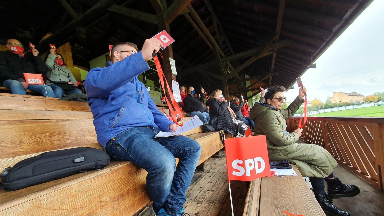 Die SPD im Wahlkreis Fürth nominiert ihren Kandidaten für die Bundestagswahl, Carsten Träger. Die Delegierten sitzen auf der Holztribüne des ASV Fürth, der Kandidat hält seine Rede unten auf dem Rasen.